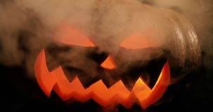 Carved Halloween pumpkin on a black background with smoke and light in mouth. Carved Halloween pumpkin lights and smoke inside with flame on a black background stock video