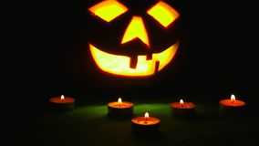 Carved Halloween pumpkin lights inside with flame on a black background with lighted candles close up.  stock footage