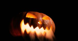Shining Jack-O-Lantern. Halloween pumpkin with scary face smoke inside with flame isolated on the black background. Carved Halloween pumpkin lights and smoke stock footage