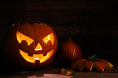 Carved halloween pumpkin with a scary glowing face on dark rusti. C wood as an autumn decoration, copy space royalty free stock images