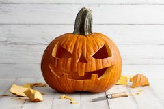 Carved Halloween pumpkin on white boards. Holiday decorations stock photo