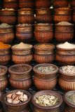 Carved handmade pots of spices, Morocco. Beautifully carved handmade pots full of aromatic spices on the marketplace. Powders, hearbs and dried berries Stock Photography