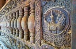 The carved handrail in Bagaya Monastery, Ava, Myanmar. AVA, MYANMAR - FEBRUARY 21, 2018: The close-up of the wooden handrail in Bagaya Monastery with complex royalty free stock photo