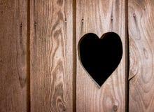 Carved heart symbol in wooden door Stock Photography