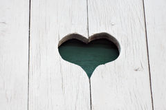 A carved heart on white wooden wall. Color photo Royalty Free Stock Image