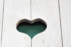 A carved heart on white wooden wall. Stock Images