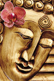 Carved image of Buddha with orchid blossom Stock Photos