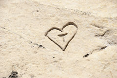 Carved initials with heart in the stone. Carved heart with initials in the rock Royalty Free Stock Photography