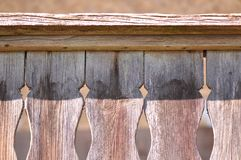 Carved motif on old wood. Traditional carved motif on a rustic old house porch royalty free stock image