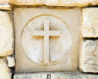 Carved out cross. Ceramic tile in old rock wall with holy cross, the christian religious symbol. Tile is one of a series of seven representing world religions in Royalty Free Stock Photography