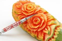 Carved papaya fruit and knife Stock Image