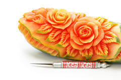 Carved papaya fruit and knife Stock Photos