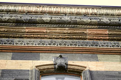 Carved pattern on the cornice and frieze of the facade. Stone wall of old building Royalty Free Stock Photo