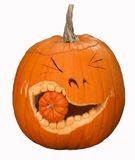 Carved pumpkin. Large carved pumpkin with smaller pumpkin in mouth royalty free stock photo