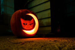 Carved pumpkin with cat and moon shape. Lighted pumpkin carved with cat and moon shape Stock Photos