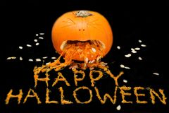 A carved pumpkin with HAPPY HALLOWEEN spelled out with the pulp stock photos