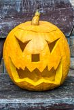 Jack-o-lantern with evil eye. A carved pumpkin lantern stands on an old wooden bench stock images