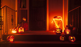 Carved pumpkin setup. Carved pumpkins and other decorations sit outside a dark house on Halloween Stock Photo