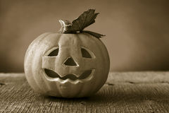 Carved pumpkin on a wooden surface, in sepia toning Stock Photos