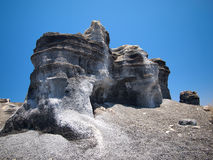 A carved rock sculpted by wind erosion against background of deep blue sky. Black lava gravel Stock Image