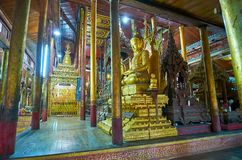 Carved sculptures in old monastery on Inle Lake, Myanmar. YWAMA, MYANMAR - FEBRUARY 18, 2018: The golden statues of Lord Buddha in prayer hall of Nga Phe Chaung Royalty Free Stock Images