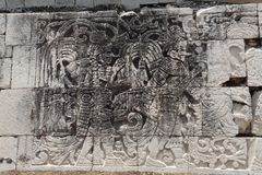 Carved Signs Chichen Itza Mexico. A carved drawing of a god and signs on a wall in the archaeological site of Chichen Itza, Yucatan peninsula, Mexico Royalty Free Stock Image