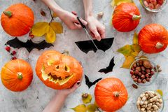Carved smiling halloween pumpkin head among pumpkins on grey background top view royalty free stock photos
