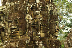 Carved stone faces at ancient temple in Angkor Wat. Heroic stone carved womens faces at ancient Angkorian temple in Angkor Wat, Cambodia. A buddhist and hindu Royalty Free Stock Photography