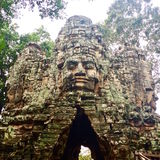 Carved stone faces ancient temple ruin. The entrance to an ancient temple complex. Stone faces overgrown with moss. At Angkor, Cambodia Stock Photography