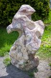 Carved stone figures of abstract shape - a beautiful decoration of the garden or park. Big stone with carved holes and abstract forms. An original decoration for royalty free stock image
