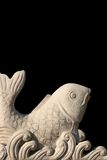 Carved stone fish. Asian style carved stone koi fish on black ground Royalty Free Stock Image