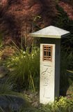 Carved stone marker in garden. Carved stone lamp post in zen garden Royalty Free Stock Images