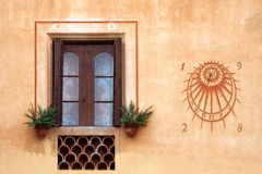 Carved sundial by window Royalty Free Stock Image