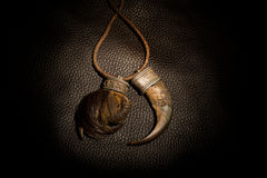 Carved tusk pendant of bone on the leather background.  Stock Photography