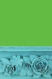 Carved Wood Flower. Carved blue flower detail on painted wooden shelf. Green background with copy space Royalty Free Stock Image