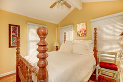 Carved wood high pole bed in bright room Royalty Free Stock Image