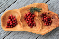 Carved wood tray with array of fresh cranberries Royalty Free Stock Image