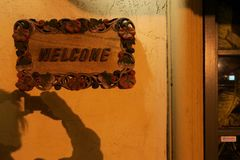Carved wood WELCOME sign with photographer shadow. Soft lamp light gives a golden hue to this attractive entrance Royalty Free Stock Photo