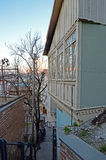Carved wooden balcony on a narrow street-stairs at sunset. Old Tbilisi, Georgia Royalty Free Stock Photography