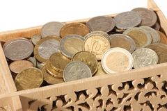 Carved wooden box filled with coins Royalty Free Stock Images