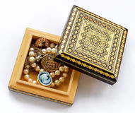 Carved wooden box with gold jewelry. Carved wooden box, gold jewelry, pendant, brooch, cameo, watches, pearl strand isolated Royalty Free Stock Images