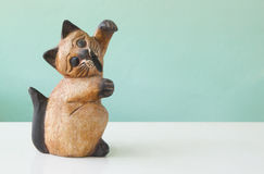 carved wooden cats on a table with green backgrounds Royalty Free Stock Photo