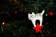 Carved Wooden Christmas Ornament of a White Kitty Cat on a Christmas Tree. Carved Wooden Christmas Ornament of a White Kitty Cat hanging on a Christmas Tree royalty free stock images