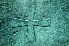 Carved wooden cross. A symbol of a cross carved on a wooden church door of turquoise color royalty free stock photo