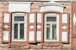 Carved wooden decorative lace decoration windows. Old wooden house. Stock Photos