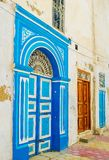 Traditional doors of residential houses, Kairouan, Tunisia. The carved wooden door with big frame, decorated with white and bright blue painted patterns, Medina Royalty Free Stock Photos