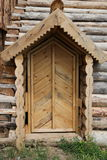 Carved wooden door. Fragment of rustic architecture. Front view of a new brown wooden door Royalty Free Stock Image