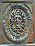Carved Wooden Door Gargoyle. Surrounded by image of snakes this Medusa Head gargoyle face is carved on an antique Parisian door royalty free stock photography