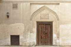 Carved wooden door and ornate doorway in Bahrain. Carved wooden door and ornate doorway in a courtyard of traditional Arabian house of pearl trader Shaikh Isa royalty free stock image