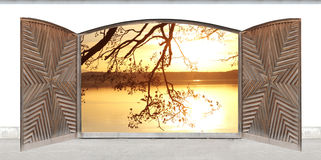 Carved wooden double door with lake view at sunset Royalty Free Stock Images